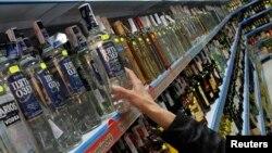 Serorang pembeli mengambil sebotol vodka dari jajaran minuman keras di sebuah supermarket di Benidorm, Rusia (Foto: dok).