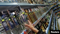 FILE - A customer takes a bottle of vodka from a shelf at a Russian supermarket in Benidorm.