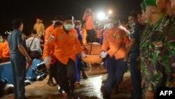 Efectivos indonesios trasladan los restos de una víctima del vuelo AirAsia estrellado recientemente.