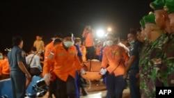 31일 쿠마이 자바 해안에서 인도네시아 구조대가 여객기에 탑승했던 사망자 시신을 이송하고 있다.