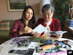 Florence Seto (right) and her granddaughter, Michelle Kalehua Kukahiko, look over family photos in Medford, Oregon.
