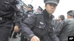 "A policeman tries to stop media from taking photos during the arrest of a man, after calls for a ""Jasmine Revolution"" protest, organized through the internet, in front of the Peace Cinema in downtown Shanghai, February 27, 2011"