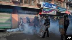 Polisi dan tentara paramiliter India berdiri di tengah-tengah gas air mata yang dilemparkan kembali oleh para pengunjuk rasa ke arah mereka di Srinagar, wilayah Kashmir yang berada di bawah kontrol India (13/11).