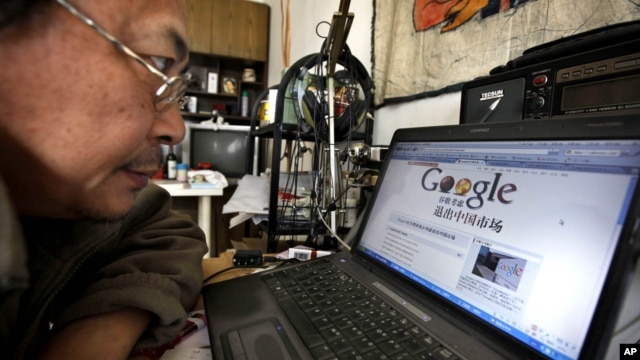 "Award winning Chinese blogger Lao Hu Miao, or Zhang Shihe, a critic of China's internet censorship, looks at a webpage with the Chinese words ""Google considers leaving the Chinese market"" in Beijing, March 23, 2010."