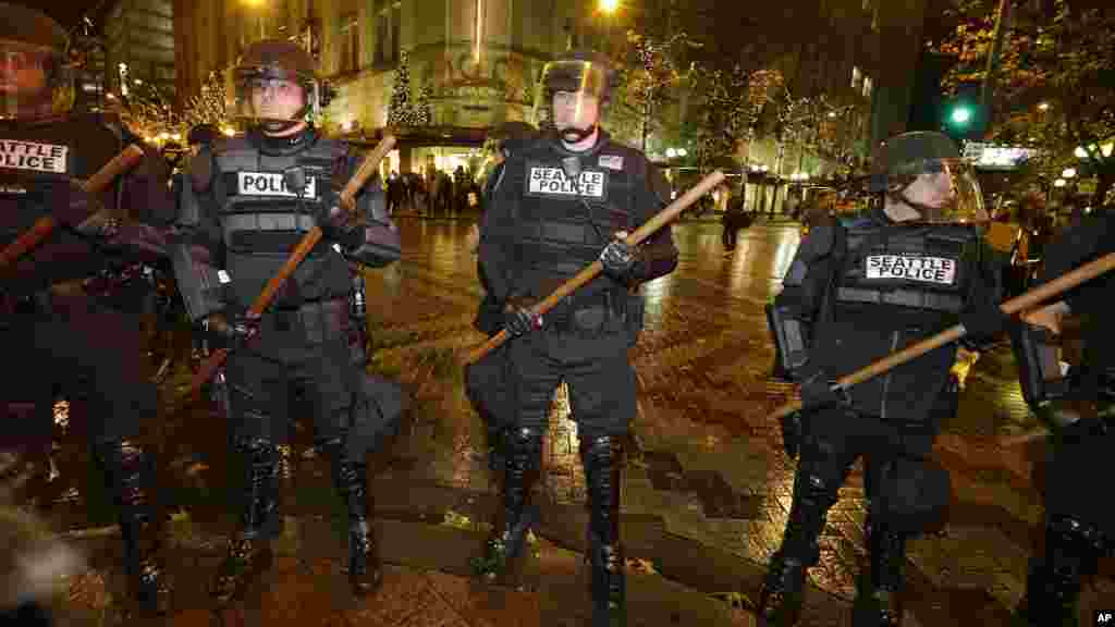 Police with wooden sticks stand guard after they cleared a group of protesters out who had stopped traffic in downtown Seattle during a demonstration against the decisions not to indict police officers who who killed men in Ferguson, Missouri and New York.