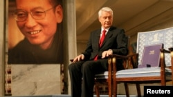 FILE - Chairman of the Norwegian Nobel Committee Thorbjoern Jagland looks down at the Nobel certificate and medal on the empty chair where this year's Nobel Peace Prize winner jailed Chinese dissident Liu Xiaobo would have sat, as a portrait of Liu is seen in the background, during the ceremony at Oslo City Hall, Dec. 10, 2010.