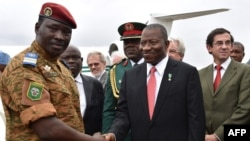 Burkina Faso's Lieutenant Colonel Isaac Zida (L) welcomes Nigerian President Goodluck Jonathan (C) next to French Ambassador Gilles Thibault (R) upon their arrival at Ouagadougou airport, Nov. 5, 2014.