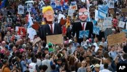 2017年5月24日,布鲁塞尔抗议者举着美国总统川普和比利时首相米歇尔的模拟像在市中心游行抗议。