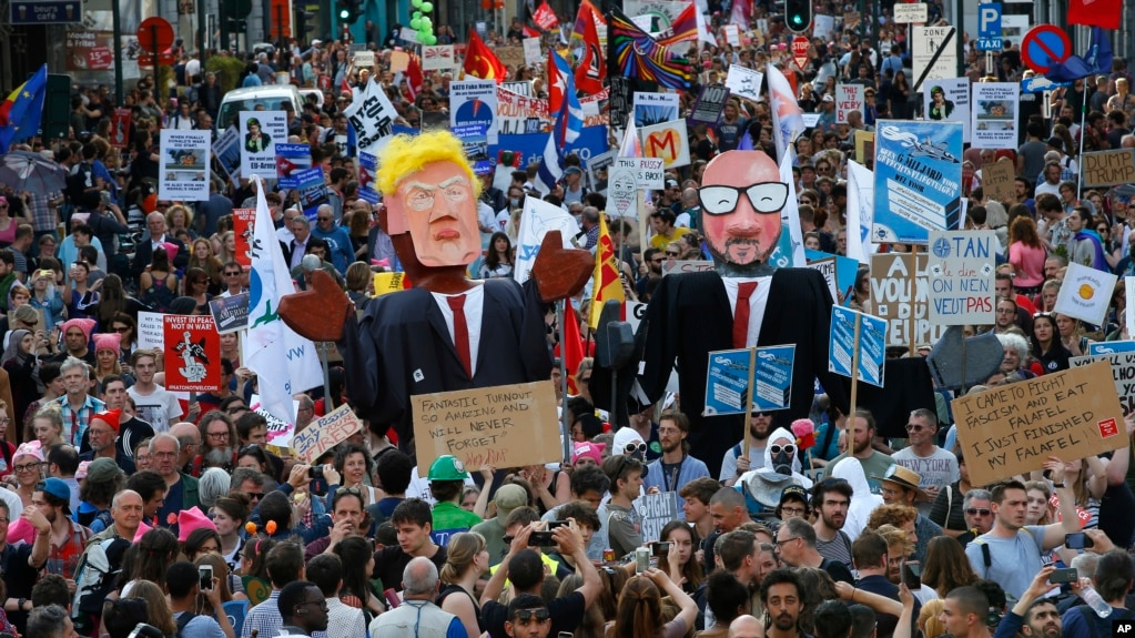 Protesters carry effigies of US President Donald Trump and Belgian PM Charles Michel during a demonstration in the center of Brussels, May 24, 2017. Demonstrators marched in Brussels ahead of a visit of US President Donald Trump and a NATO heads of state summit that will take place Thursday.