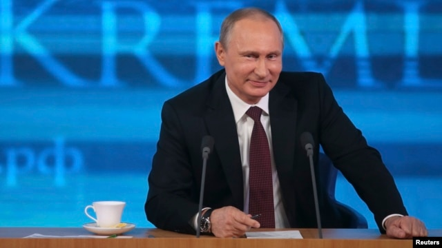 Russian President Vladimir Putin smiles as he takes part in a televised news conference in Moscow, Dec. 19, 2013.