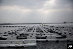FILE - Contractors work on a floating solar panel array on the Queen Elizabeth II Reservoir near Walton-on-Thames in southwest London, March 21, 2016. Britain's unique climate is seen as having contributed to its reaching its current capacity of renewables.