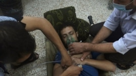 A man, affected by what activists say is nerve gas, breathes through an oxygen mask in the Damascus suburbs of Jesreen, Aug. 21, 2013.