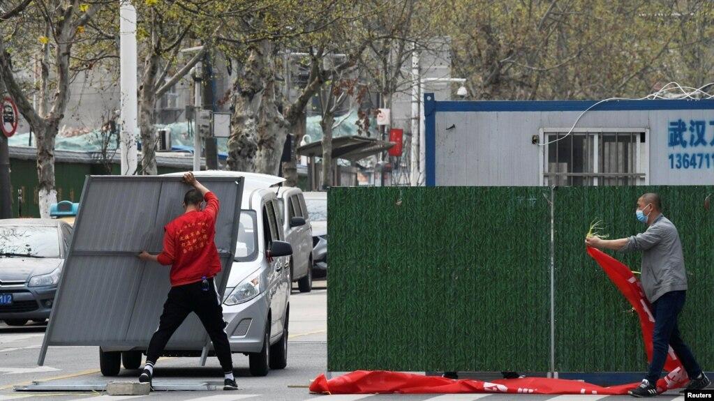 Công nhân đang dỡ bỏ các rào chắn trên đường phố ở Vũ Hán sau khi thành phố tâm dịch Covid-19 nới lỏng lệnh phong tỏa.