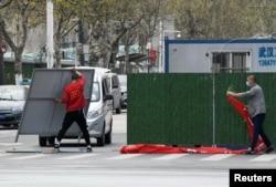 戴着口罩的工人正在拆除武汉街头的障碍物。(2020年3月21日)