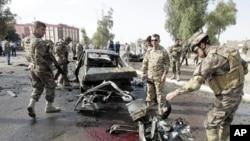 伊拉克安全部队士兵4月19日在基尔库克检查血迹斑斑的汽车炸弹爆炸现场