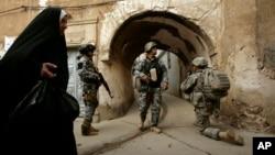 ແມ່ຍິງ ອີຣັກ ຄົນໜຶ່ງຍ່າງຜ່ານທະຫານ ແລະ ຕຳຫຼວດ ອີຣັກ ໃນຂະນະທີ່ພວກເຂົາເຈົ້າຢືນຍາມ ໃນເຂດ Bab al-Jadeed ໃນເມືອງ Mosul, 360 ກິໂລແມັດ ທາງພາກຕາເວັນຕົກສຽງເໜືອ ຂອງນະຄອນຫຼວງ ແບກແດັດ, ອີຣັກ.