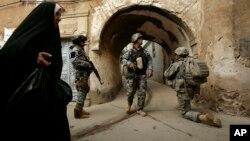 Hình tư liệu - Lính Hoa Kỳ và cảnh sát Iraq đứng bảo vệ bên ngoài khu vực Bab al-Jadeed, Mosul, Iraq.