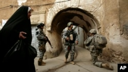 一名伊拉克婦女走過在摩蘇爾地區一個警察局站崗的美軍士兵。(資料照片)