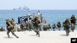 FILE - Philippine and U.S. Marines storm a beach as part of an amphibious landing exercise, May 9, 2018, during a two-week joint U.S.-Philippines exercise facing the South China Sea in the Philippines.