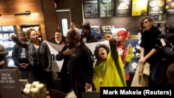 Manifestantes protestan dentro de Center City Starbucks, donde dos hombres negros fueron arrestados, en Filadelfia, Pensilvania, el 16 de abril de 2018. REUTERS / Mark Makela