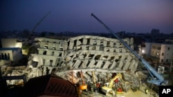In the early morning, emergency rescuers continue to search for the missing in a collapsed building from an earthquake in Tainan, Taiwan, Feb. 7, 2016.