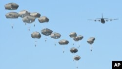 Airborne forces from the U.S., Great Britain and Poland conduct a multi-national jump on to a designated drop zone near Torun, Poland, June 7, 2016. The exercise, Swift Response-16, sets the stage in Poland for the multi-national land force training event