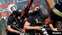 FILE - A Turkish riot policeman pushes a photographer during a protest at Taksim Square in Istanbul, June 11, 2013.