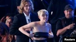 """Miley Cyrus camina frente a su amigo Jesse Helt, (Izq.), a quien presentó al recibir el premio a Mejor Vídeo del año, por la canción """"Wrecking Ball"""", en la gala de los premios MTV."""