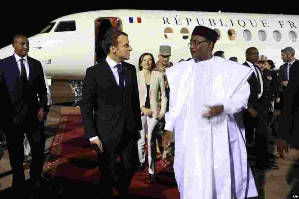 Le président français Emmanuel Macron et la ministre française de la Défense, Florence Parly, sont accueillis par le président du Niger Mahamadou Issoufou à leur arrivée à l'aéroport de Niamey le 22 décembre 2017.