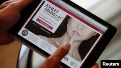 Pendiri Ashley Madison, Noel Biderman, menunjukkan lamannya di sebuah tablet dalam sebuah wawancara dengan media di Hong Kong. (Foto: Dok)