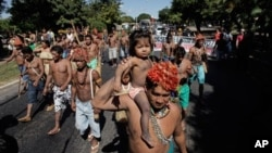 Munduruku Indians march to the Ministry of Mines and Energy, in Brasilia, Brazil, Tuesday, June 11, 2013. The group along with other had been occupying the controversial Belo Monte dam being built in the Amazon on the Xingu River. They were recently flown