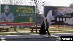 FILE - Pedestrians pass by a billboard with a picture of imprisoned Kurdish rebel leader Abdullah Ocalan in Diyarbakir, Feb. 11, 2014.