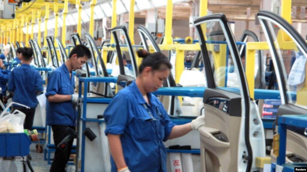 在中國廣西壯族自治區柳州市的通用五菱汽車工廠,員工在一條生產線上工作(2016年6月19日)。 而在中國的有些生產線上,例如杭州中恆電氣公司的生產線上,工人們戴著用於監控他們腦電波的帽子。