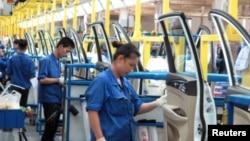 在中国广西壮族自治区柳州市的通用五菱汽车工厂,员工在一条生产线上工作(2016年6月19日)。而在中国的有些生产线上,例如杭州中恒电气公司的生产线上,工人们戴着用于监控他们脑电波的帽子。