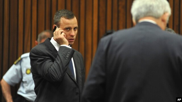 Oscar Pistorius talks on a mobile phone while waiting for proceedings to get under way in court in Pretoria, South Africa, March 24, 2014.
