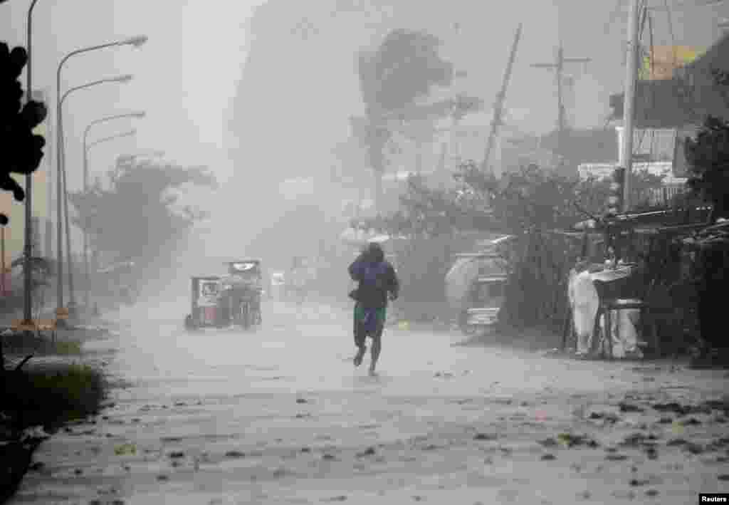A man walks on a street while strong winds and heavy rain, brought by typhoon Hagupit, batter Atimonan town, Quezon province, south of Manila, December 8, 2014.