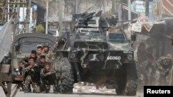 ທະຫານລັດຖະບານ ເຂົ້າຫາບ່ອນປ້ອງກັນ ໃນລະຫວ່າງ ການຍິງຕໍ່ສູ້ ກັບພວກກະບົດມຸສລິມ ຈາກກຸ່ມ Moro National Liberation Front (MNLF) ໃນເມືອງ Zamboanga, ພາກໃຕ້ຂອງ ຟີລິບປິນ. 12 ກັນຍາ, 2013.