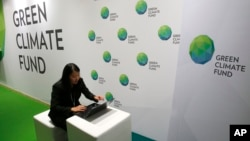 A woman works her computer at the Green Climate Fund stand at the COP21, United Nations Climate Change Conference, in Le Bourget, north of Paris, Nov. 30, 2015.