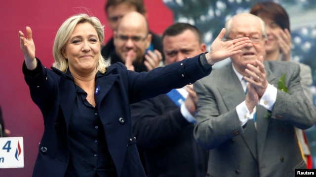 FILE - France's far right National Front political party leader Marine Le Pen (L) gestures at supporters.