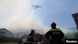 A firefighting plane drops water to extinguish a fire in village of Strinjine near Split, Croatia, July 18, 2017.