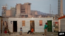 People sitting outside their shacks in the Nkaneng shantytown next to the platinum mine, run by British company Lonmin, in Marikana. South Africa, July 9, 2913.