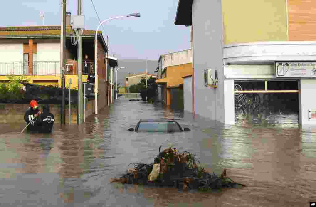 Rescuers work in a flooded street in the small town of Uras, Sardinia, Italy, Nov. 18, 2013.