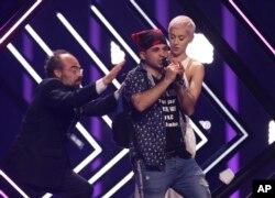 ຊາຍຄົນນຶ່ງ ຈັບເອົາໄມໂກຣໂຟນ ຂອງນາງ ຊູຣີ ຈາກອັງກິດ, ຂວາ, ໃນຂະນະທີ່ ພະນັກງານຮັກສາຄວາມສະຫງົບ ຟ້າວເຂົ້າໄປຄວບຄຸມໂຕຊາຍຄົນນັ້ນ ຢູ່ທີ່ນະຄອນລິສບອນ ຂອງປອກຕຸຍກາລ, ວັນທີ 12 ພຶດສະພາ 2018 ໃນລະຫວ່າງ ການແຂ່ງຂັນຮ້ອງເພງ Eurovision ຮອບສຸດທາຍ.