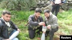 Borci pobunjeničke Slobodne sirijske armije pripremaju minobacačke granate za borbu, u Huli, nedaleko od grada Homsa