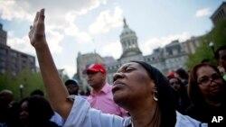 Patricia Freeman ora durante una manifestación frente a la alcaldía de Baltimore, el domingo, luego de ser levantado el toque de queda.