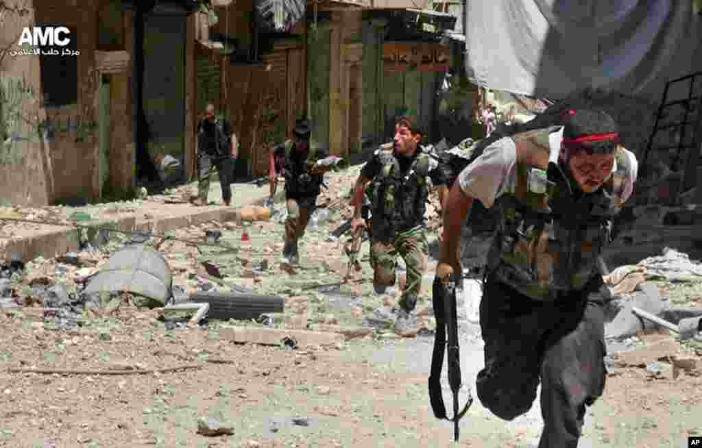 This citizen journalism image provided by Aleppo Media Center AMC shows Syrian rebels running during heavy clashes with Syrian soldiers in the Salah al-Din neighborhood of Aleppo, Syria, July 9, 2013.