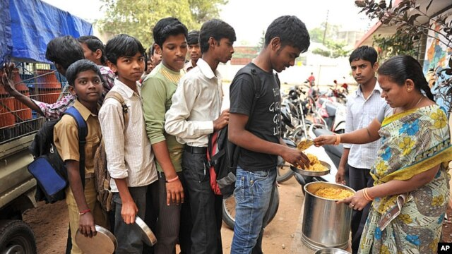 An Indian teacher serves the mid-day meal to children at a Government High School in Hyderabad, January 10, 2012.
