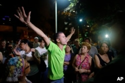 FILE - An opposition supporter celebrates the closing of a polling station during congressional elections in Caracas, Venezuela, Dec. 6, 2015.