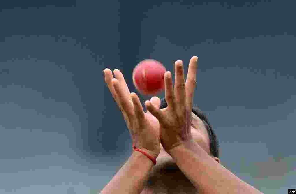 កីឡាករ Cricket លោក Subashis Roy ចាប់បាល់មួយក្នុងពេលហ្វឹកហាត់នៅកីឡដ្ឋាន R. Premadasa Stadium រដ្ឋធានីកូឡុំបូ មុនពេលប្រកួតក្នុងប្រទេសស្រីលង្កា។