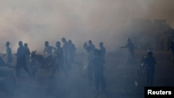 Palestinians react to tear gas fired by Israeli troops during a protest at the Israel-Gaza border in the southern Gaza Strip, July 13, 2018.